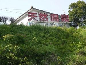 三川内IC上の小高い丘の上に「天然温泉」の看板が見えます。